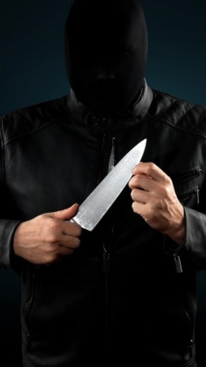 Homem encapuzado segura faca
